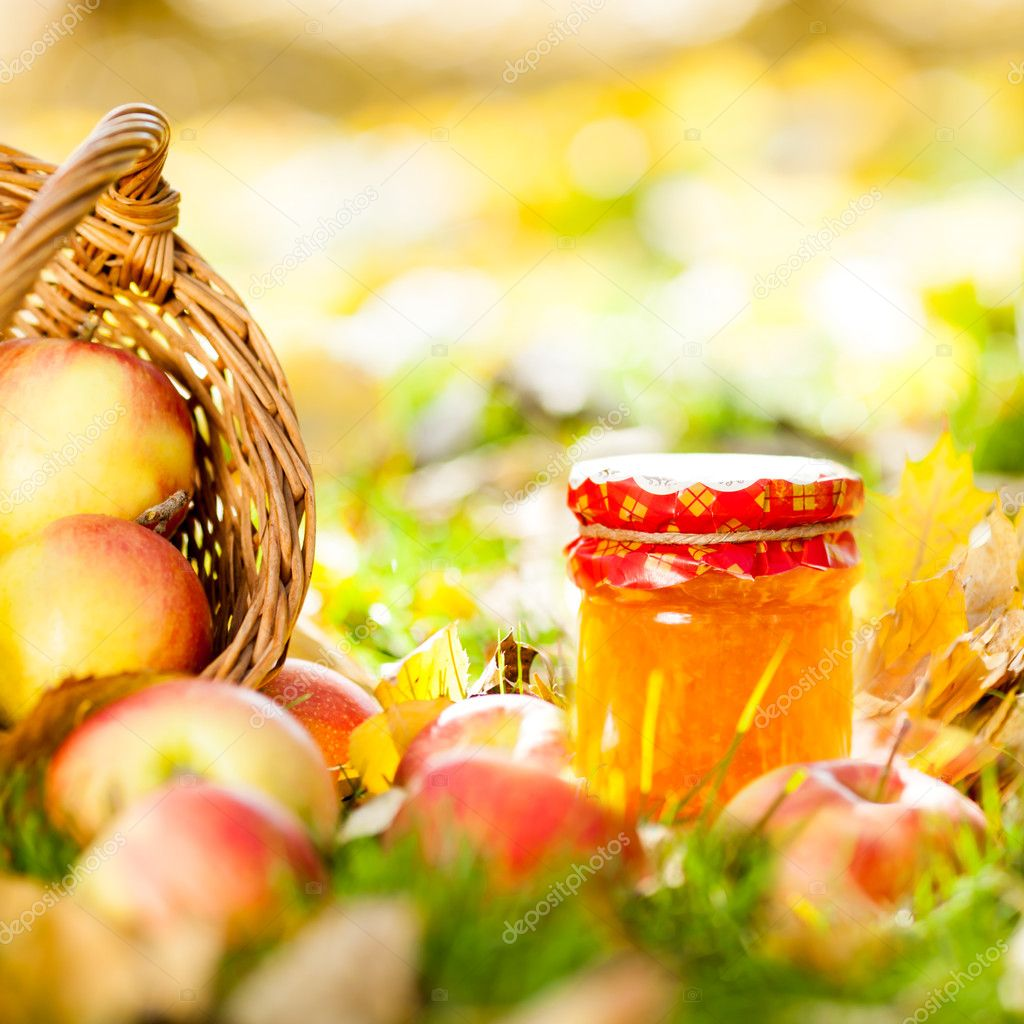 Autumn background with jam in jar and red juicy apples on yellow leaves outdoors — Stock Photo #10909710