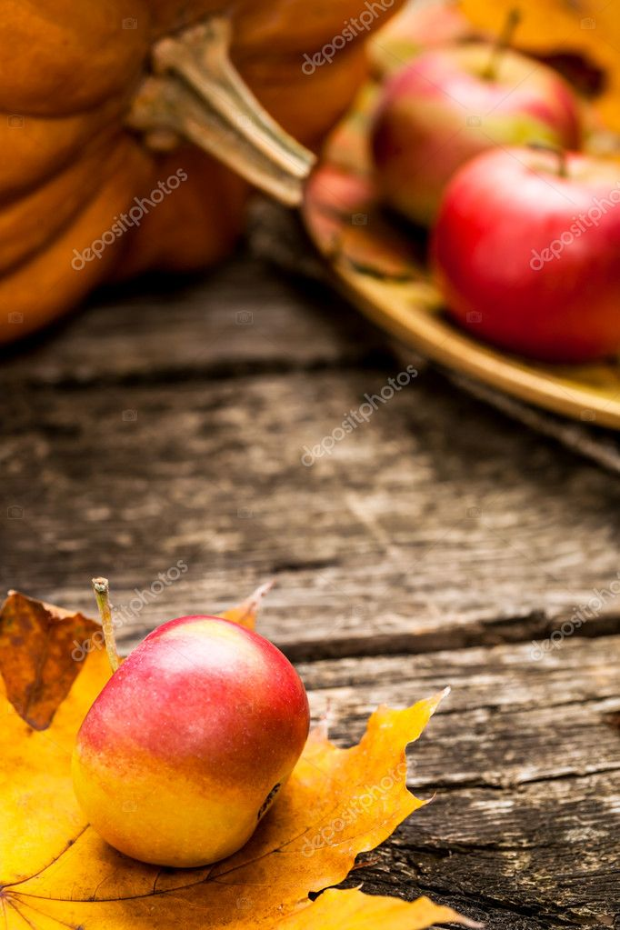 Autumn background with apples, pumpkin and maple leaf on old wooden table. Thanksgiving day concept. Shallow depth of fields — Stock Photo #10909753