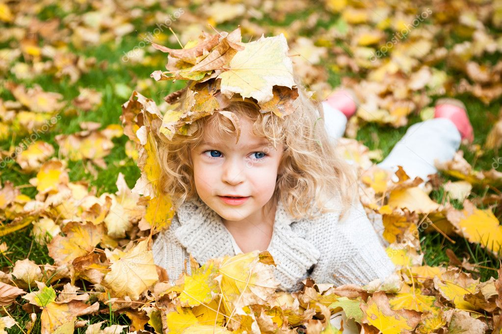 Smiling child in autumn yellow leaves outdoors. Autumn fashion concept  Foto Stock #10909809