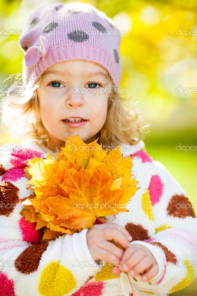 Happy smiling child with yellow maple leaves in autumn park  Stock Photo #10909853