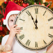 Kid hiding by old wooden clock — Stock Photo