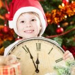 Royalty-Free Stock Photo: Kid in Santa's hat holding vintage clock