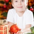 Foto Stock: Smiling boy holding Xmas ball