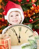 Kid i santa hatt hålla vintage klocka — Stockfoto