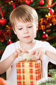 Boy opening Xmas present — Stock Photo