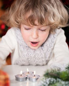Beautiful child blowing out candles — Stock Photo