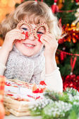 Funny child holding handmade Xmas decorations — Stock Photo