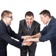 Three laughing partners putting their hands on the top isolated — Stock Photo