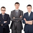 Three young smiling business men standing with folded hands isol — Stock Photo