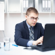 Portrait of young business man working on a laptop at office — Stock Photo #11589256
