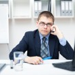 Young businessman talking on a cell phone at office — Stock Photo #11589266
