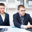 two young businessmen working together with laptop at office des — Stock Photo