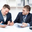 Two laughing young businessmen working together in office — Stock Photo