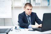 Młody biznesmen działa na laptopie w urzędzie — Zdjęcie stockowe