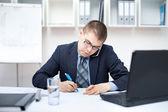 Portrét mladé obchodní člověka v kanceláři, dělat některé paperwor — Stock fotografie