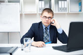 Young businessman talking on a cell phone at office — Stock Photo