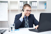 Portrait of smiling young business man talking on cell phone and — Stock Photo