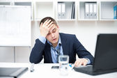 Thoughtful or stressful businessman at work — Stock Photo