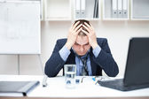Depressed young business man holding his head at office — Stock Photo