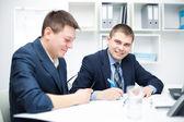 在办公室一起工作的两个快乐年轻商务男士 — 图库照片