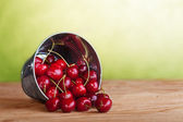 Cherries in a bucket on old wooden table — Stock Photo