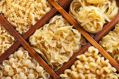 Assorted pasta in wooden compartments — Stock Photo