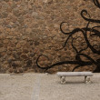 Stock Photo: Old stone wall with bench and graffiti