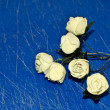 Artificial white rose on blue background. — Stock Photo