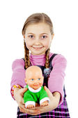 Little schoolgirl plays with a doll — Stock Photo