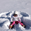 Girl lies on snow. Snow angel — Stockfoto