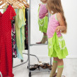 Stock Photo: Little girl trying on large shoes