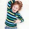 Young boy fooling around and playing on floor — Stock Photo #10787610