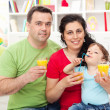 Family with child having fruit juice — Stock Photo