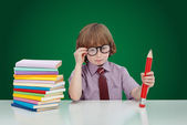 Boy genius with books and large pencil — Stock Photo
