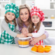 Woman and kids making fresh fruit juice — Stock Photo