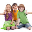 Three kids giving thumbs up sign - Stock Photo