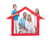Young family with two kids holding house sign — Stock Photo