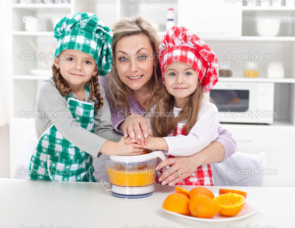 Woman and kids making fresh fruit juice - dressed as chefs in the kitchen  Stock Photo #10984870