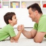 Постер, плакат: Father and son arm wrestling
