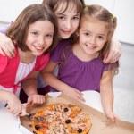 Three girlfriends sharing a pizza — Stock Photo