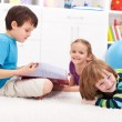 Stock Photo: Kids reading a book and having fun