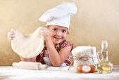 Little girl making pizza or pasta dough — Stock Photo
