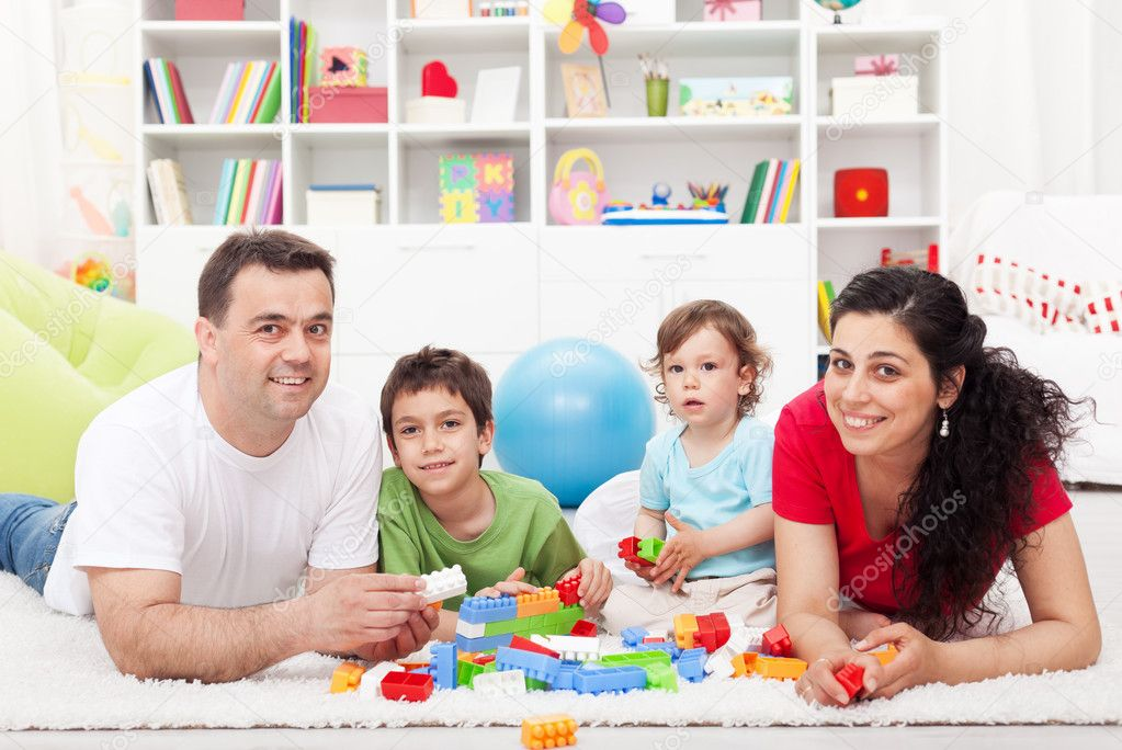 Kids with their parents playing at home - family portrait, focus on the children — Stock Photo #11656786
