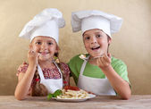 Happy kids with chef hats eating fresh pasta — Stock Photo