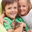 Happy kids with their new pet - a little kitten — Stock Photo