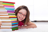 Young student with lots of books smiling — Stock Photo
