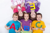 Group of kids holding alphabetical letters — Stock Photo