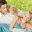 Young couple reading together, outdoor — Stock Photo
