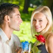 Young couple with gifts, rosa and champagne, outdoor — Stock Photo #10795368