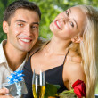 Young couple with gifts, rosa and champagne, outdoor — Stock Photo #10795374